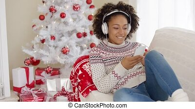 Attractive woman listening to music at Christmas -...