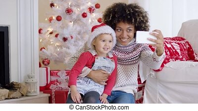 Woman and child posing for camera phone in front of white...