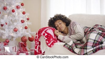 Woman sleeping on couch beside Christmas tree - Single Black...