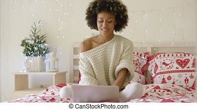 Happy woman in sweater on bed using computer - Single happy...