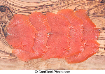 Smoked wild pacific sockeye salmon on olive wood cutting...