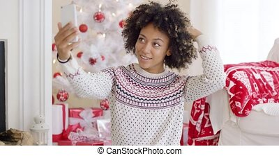 Young woman posing for a Christmas selfie in a red and white...