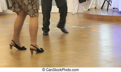 Woman and man dancing at a wedding indoors. People's feet...