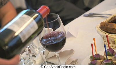 Waiter pouring red wine into a glass