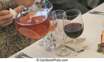 Waiter pouring glass of berry juice from pitcher - Waiter...