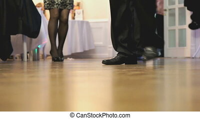 People dancing at the party indoors. People's feet close up