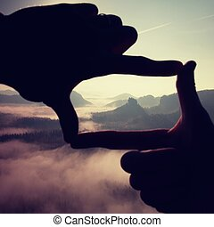 Fingers frame. Close up of hands making frame gesture. Blue misty valley bellow rocky peak. Sunny spring in rocky mountains.