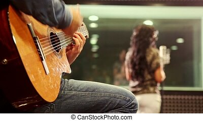 Closeup Guy Plays Guitar Girl Sings at Rehearsal in Studio -...
