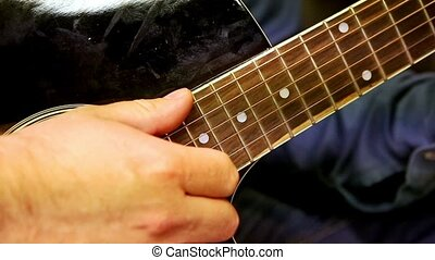 Closeup Guy Plays Guitar Strings at Rehearsal in Studio -...