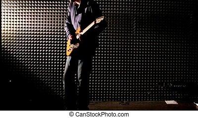 Guy Plays Guitar at Rehearsal in Dark Studio - caucasian guy...
