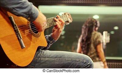Closeup Guy Plays Guitar Girl Sings at Rehearsal in Studio -...