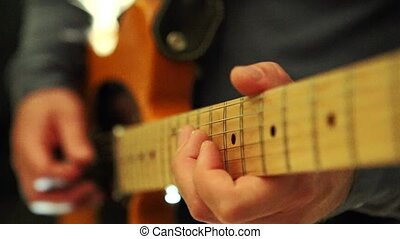 Closeup Guy Runs Fingers Slowly over Guitar Neck in Studio -...