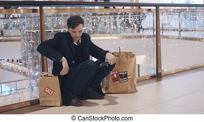 Disappointed young man sitting on the floor in mall without...