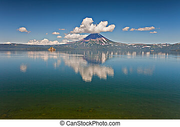 Volcano and lake with reflection in water in Russia on...