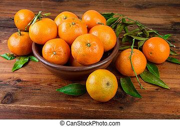 Mandarins tangerines in brown ceramic bowl