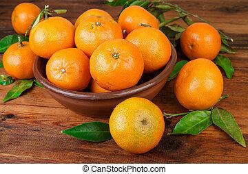 Tangerines in brown ceramic bowl closeup