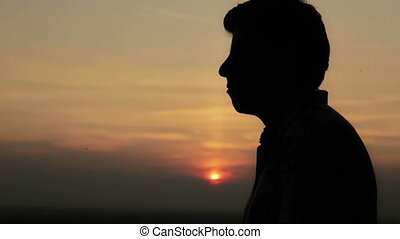 Young man praying at sunset - Silhouette of young man...