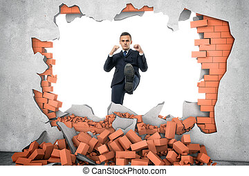 Businessman ruins brick wall with his leg on the white...