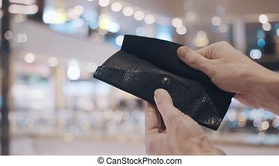 Man hands pulls out stiker with red SALE inscription from empty wallet. After Black Friday sales