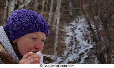 Girl eating cake and drinks tea at a stream in the winter...