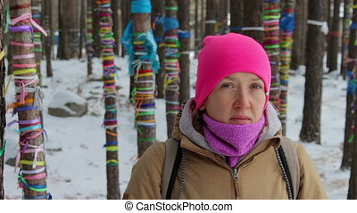 Portrait of a girl in the winter forest among the trees with colored ribbons