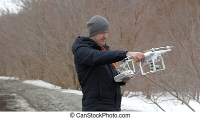 A man with a drone in hands preparing to flight. Compass...