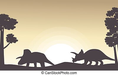 Silhouette of two triceratops on the hill scenery