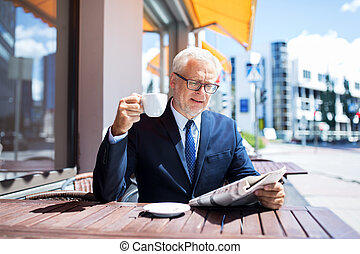 senior businessman with newspaper drinking coffee -...