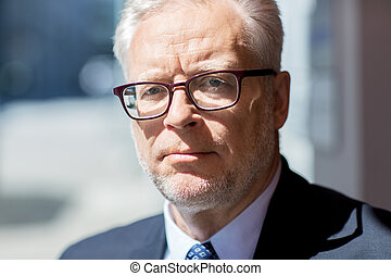 close up of senior businessman in eyeglasses - business and...