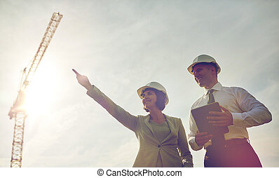 happy builders in hardhats with tablet pc outdoors -...
