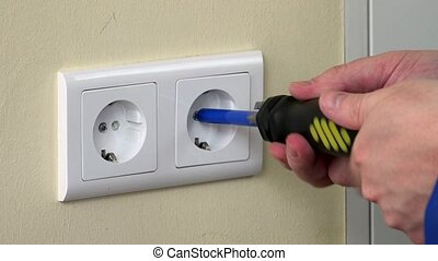 male hands with screwdriver repairing electrical outlet on...