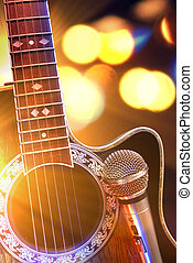 Acoustic guitar and microphone with lights in the...
