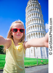 Little girl taking selfie background the Leaning Tower in Pisa, Italy