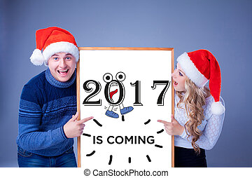 Christmas couple holding white board with empty copy space