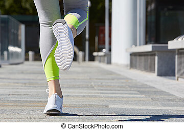 Woman running in the city in a sunny morning - Woman running...