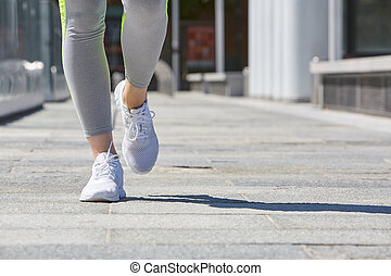 Woman running in the city with tracksuit and shoes, sunlight...