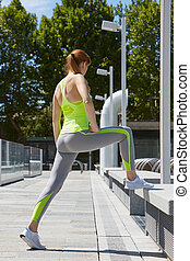 Woman stretching in the city before running, sunlight -...