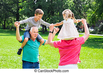 Grandparents Giving Grandchildren Piggyback Ride In Park