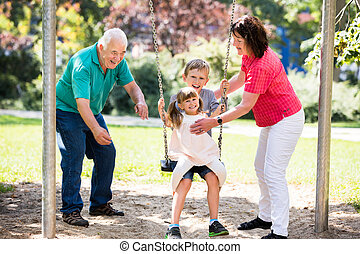 Happy Granddaughter Preparing For Swing With Their Grandparent
