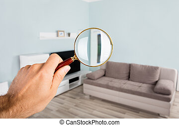Person Checking Living Room Using Magnifying Glass -...