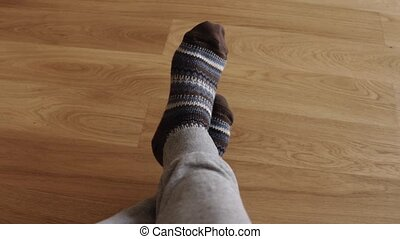 Man's feet wearing warm knitted socks. Warm, winter and...