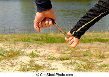 Hand of father and  baby in black shirt  holding small spruce twig. Pond or lake in background