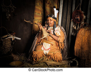 Storyteller in wigwam - Weathered mature tribal female...