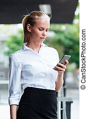 Blonde businesswoman texting message while standing outdoors...