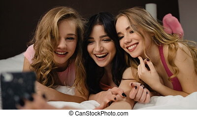 Three beautiful smiling curly friends with similar nails...