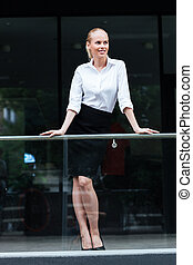 Portrait of a smiling businesswoman leaning on the glass railing