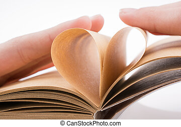 Heart on notebook - Hand making a heart from pages of a...