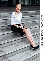 Young woman with a laptop sitting on the stairs - Full...
