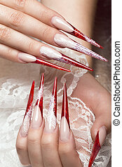 Long beautiful manicure with lace on female fingers. Nails design. Close-up