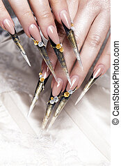 Long beautiful manicure with flowers on female fingers. Nails design. Close-up